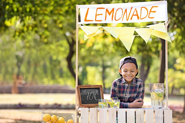 Little African-American boy at lemonade stand in park